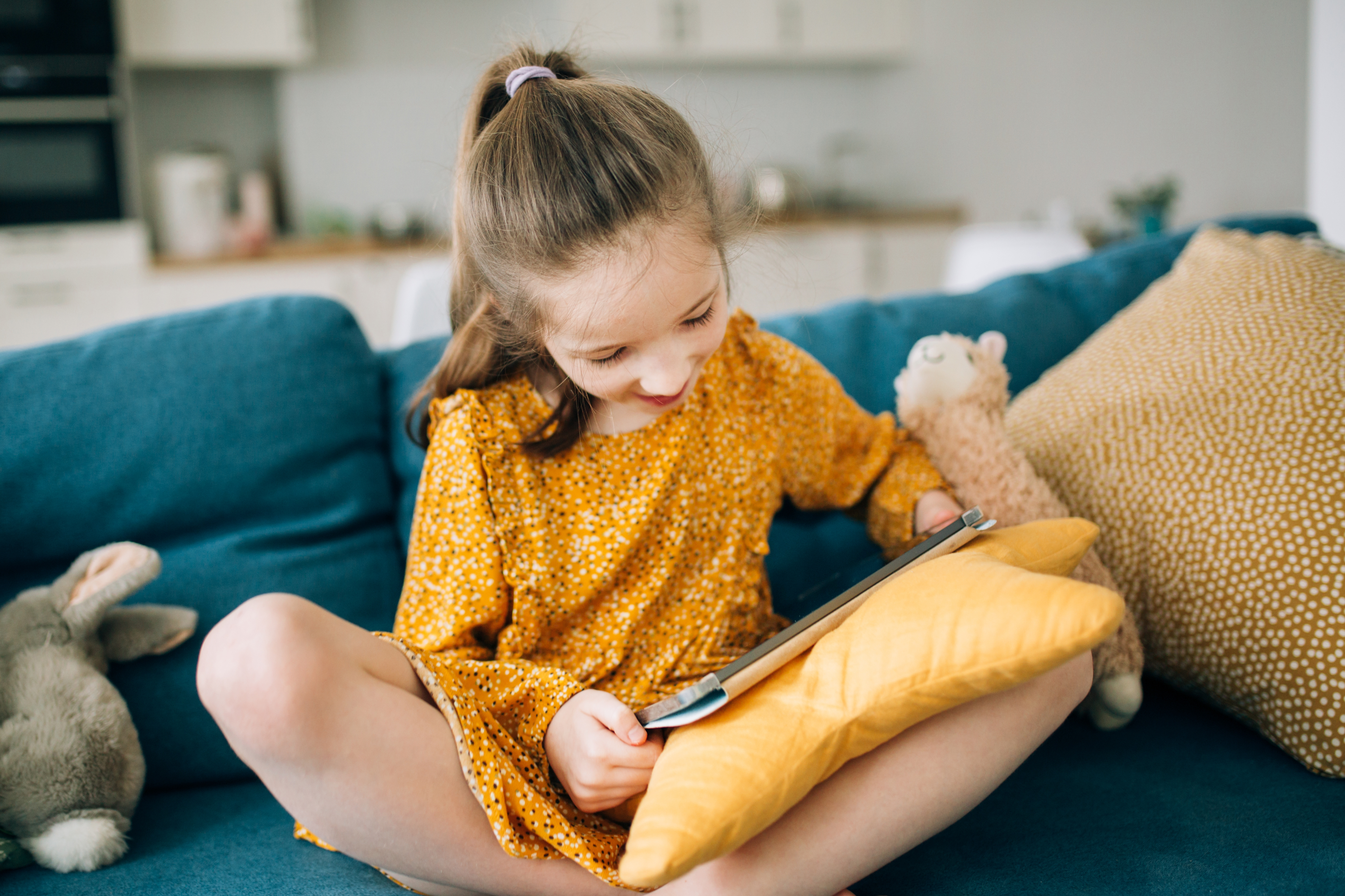 a-girls-is-sitting-on-a-sofa-with-tablet-and-toys-SCK855W